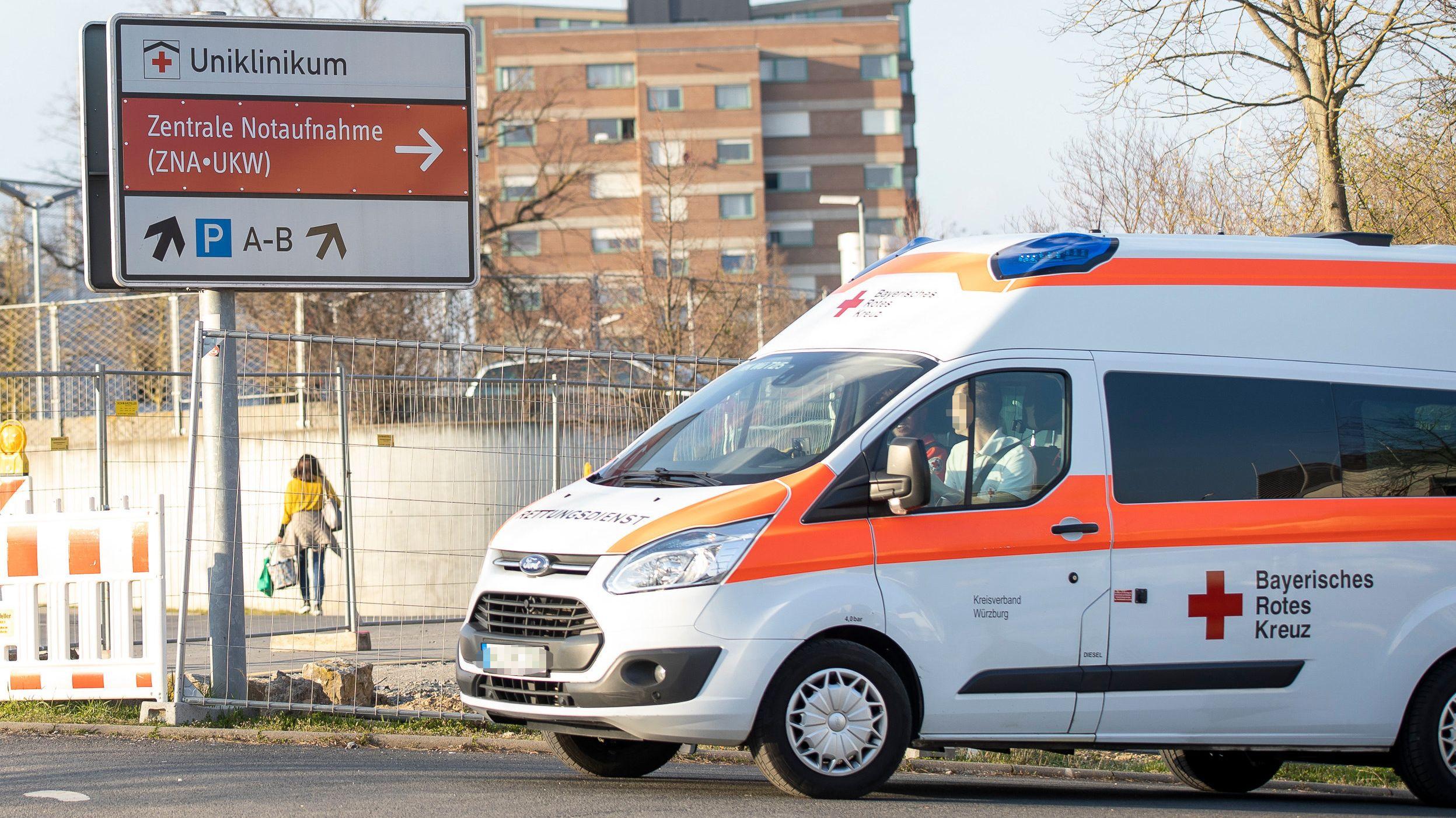 Ein Rettungswagen steht vor einem Schild, das auf die Uniklinik Würzburg hinweist.
