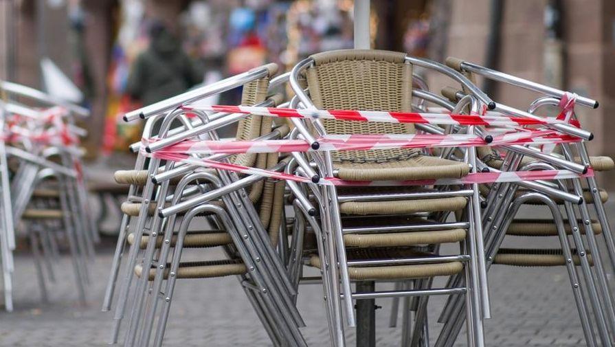 Stühle eines Restaurants stehen mit Absperrband zusammengebunden auf dem Gehweg.