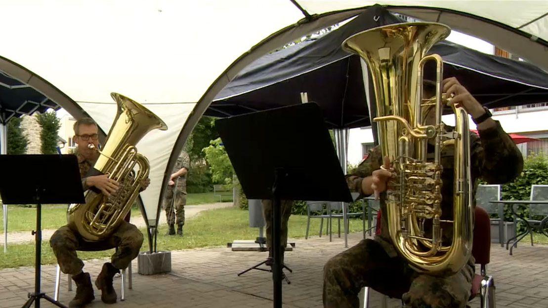 Zwei Männer der Bundeswehr spielen auf Blechblasinstrumenten vor einem Seniorenheim
