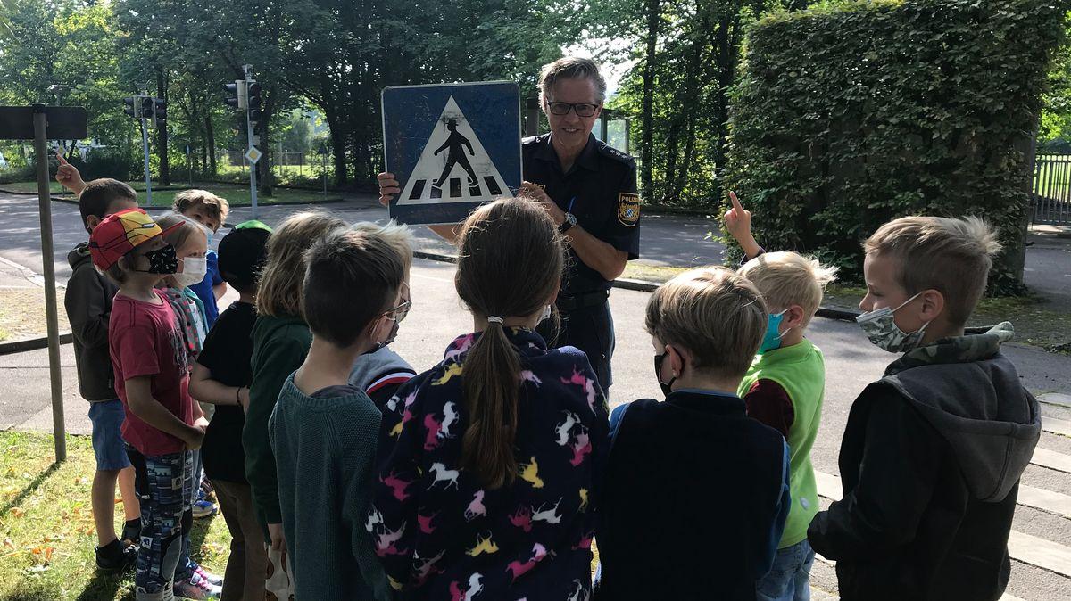 Ein Polizist vor mehreren Kindern hält ein Verkehrsschild hoch.