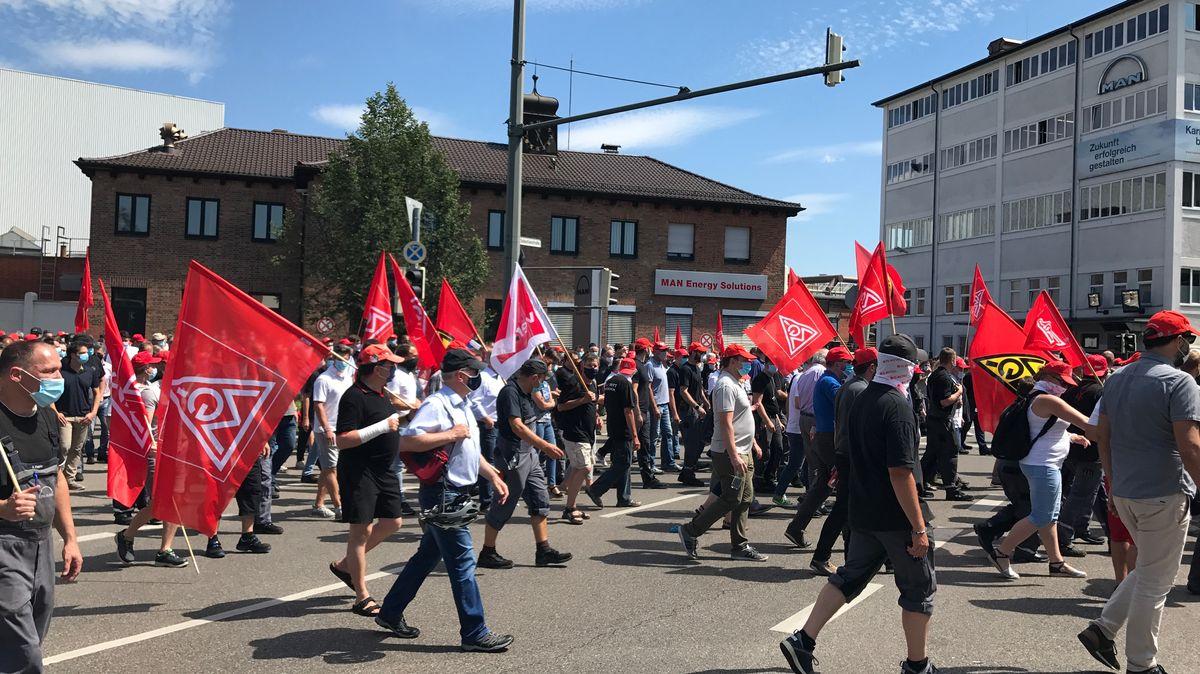 Demonstranten mit Fahnen laufen vor dem MAN-Gebäude vorbei.