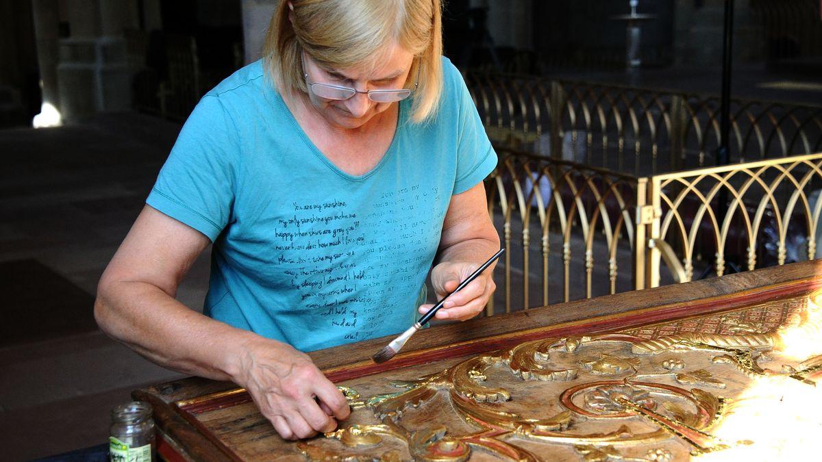Eine Frau arbeitet an einem alten Kunstwerk.