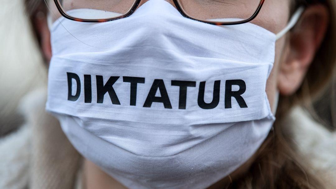 """Bremen: Eine Demonstrantin trägt eine Maske mit der Aufschrift """"Diktatur""""."""