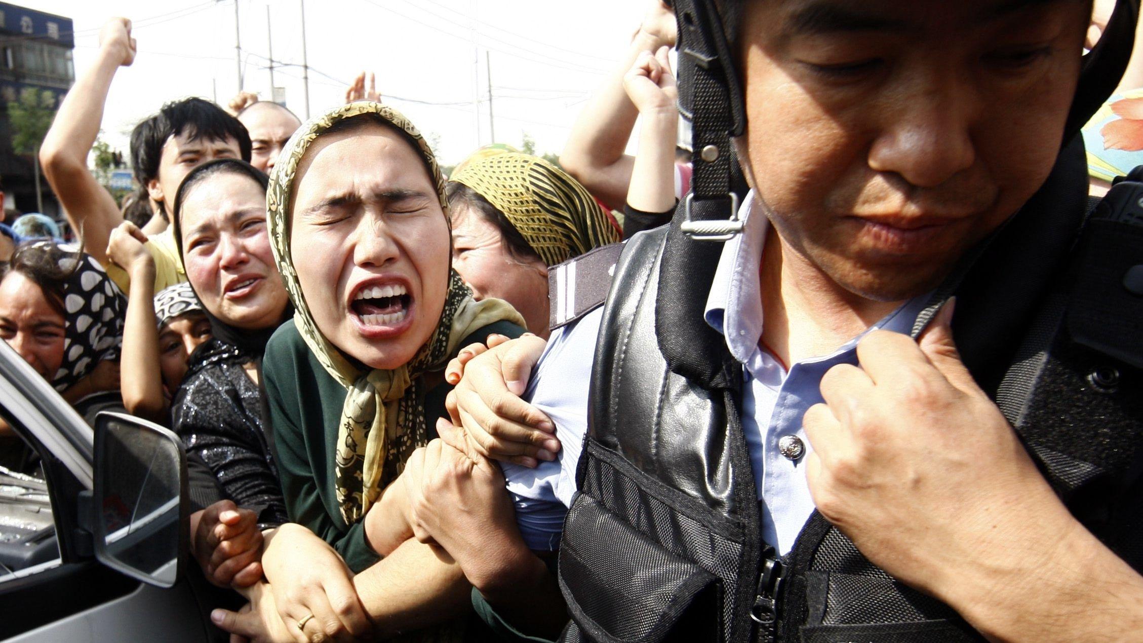 Eine Gruppe verzweifelter Menschen hinter einem Polizisten in Uniform. Der Polizist ist von der Gruppe weggedreht, obwohl ihn zahlreiche Hände berühren.