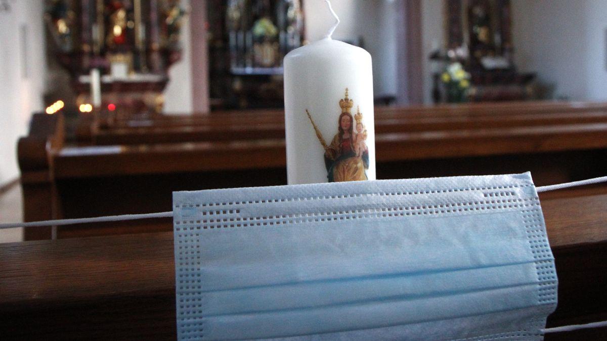 Eine Mund-Nasen-Bedeckung vor einer Kerze in den Bankreihen einer Kirche