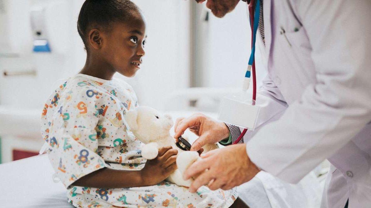 Mädchen mit Teddy wird beim Arzt untersucht