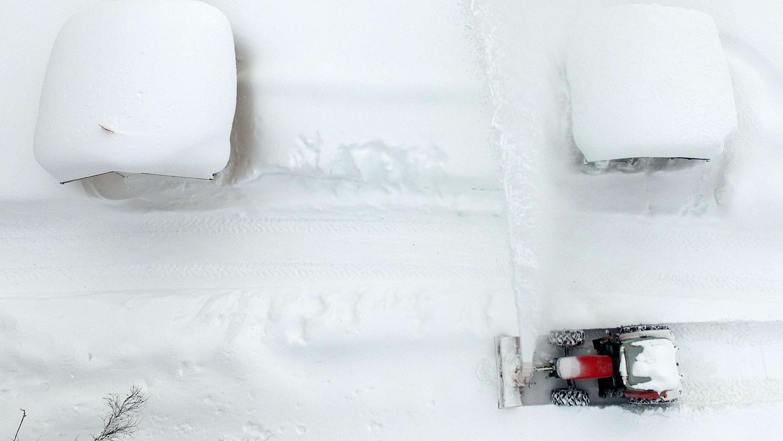 Ramsau, Österreich: Die Luftaufnahme zeigt einen Schneepflug beim Räumen einer Straße