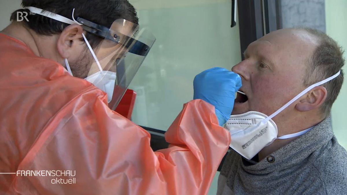 Ein medizinischer Mitarbeiter nimmt bei einem Mann einen Abstrich vor.