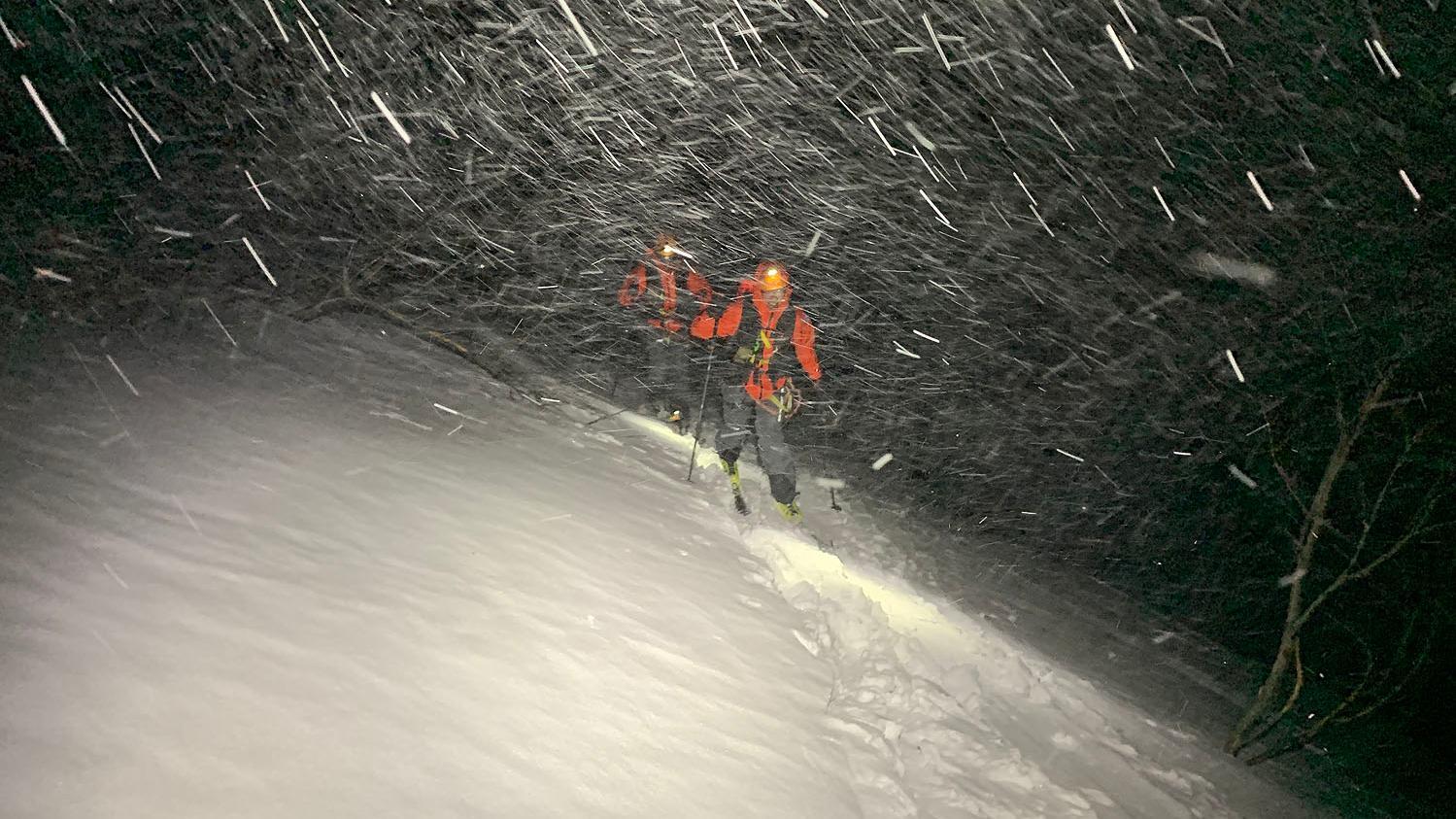 Bergretter helfen einem Skitourengeher.