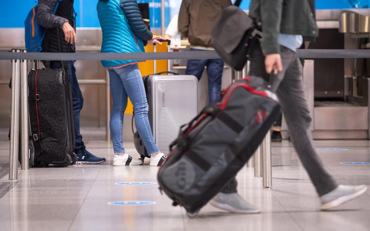 26.03.2021, Bayern, München: Reisende stehen am Flughafen München mit ihren Koffern an einem Check-In Schalter. Die generelle Corona-Testpflicht für Einreisen per Flugzeug nach Deutschland soll erst in der Nacht zum 30.03.21 in Kraft treten. Foto: Sven Hoppe/dpa +++ dpa-Bildfunk +++