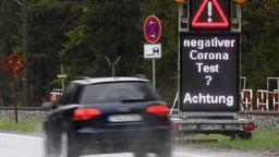 Ein Auto fährt an einem Hinweisschild zur Corona-Testpflicht vorbei | Bild:dpa/picture alliance