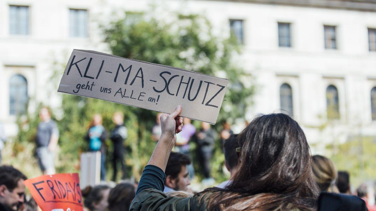 """""""Klimaschutz geht uns alle an!"""" steht auf einem Schild einer Demonstrantin während eines Klimastreiks"""