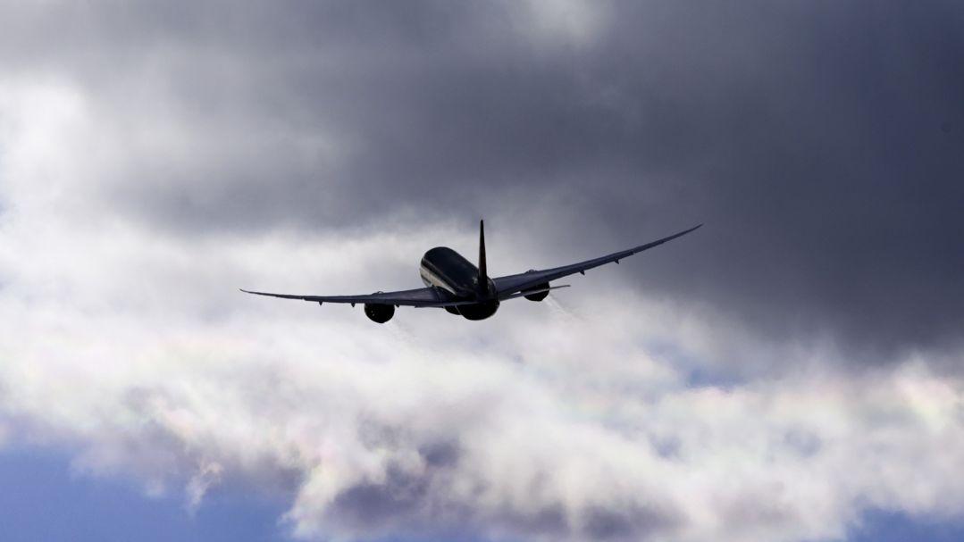Eine Boeing 787 Dreamliner vor dunklen Wolken.