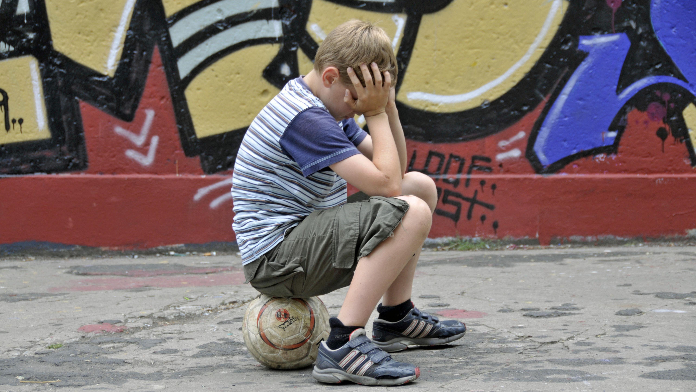 Ein Junge sitzt auf einem Fußball (Symbolbild).
