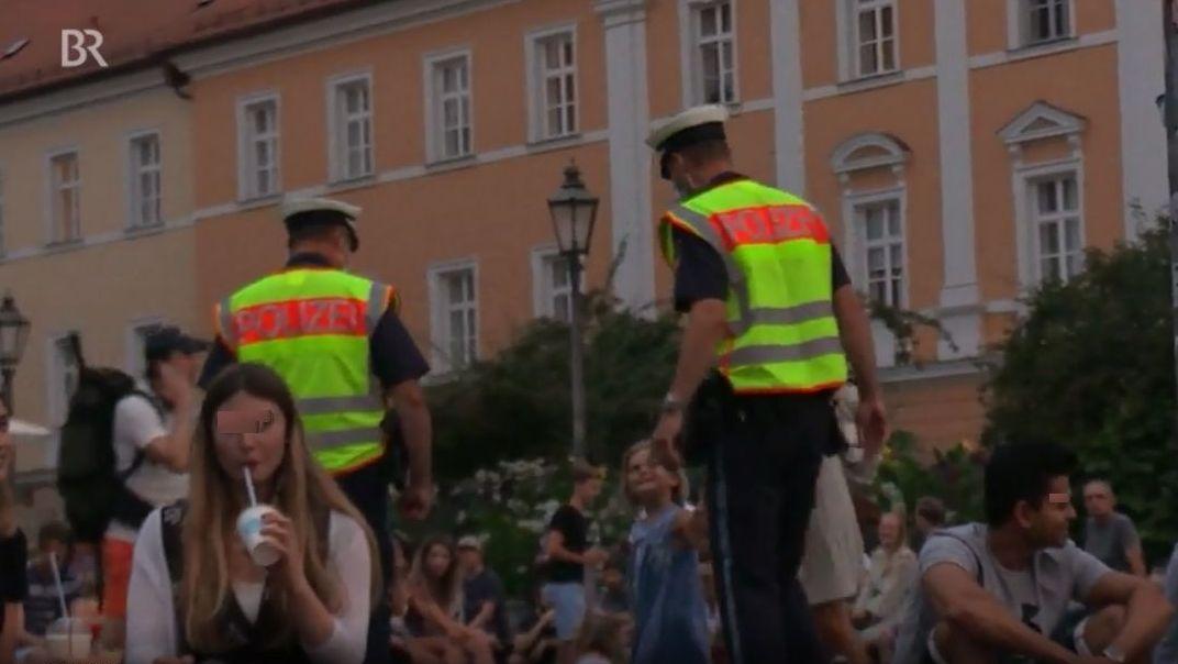 Polizeibeamten kontrollieren die Einhaltung der Corona-Regeln auf dem Bismarckplatz in Regensburg