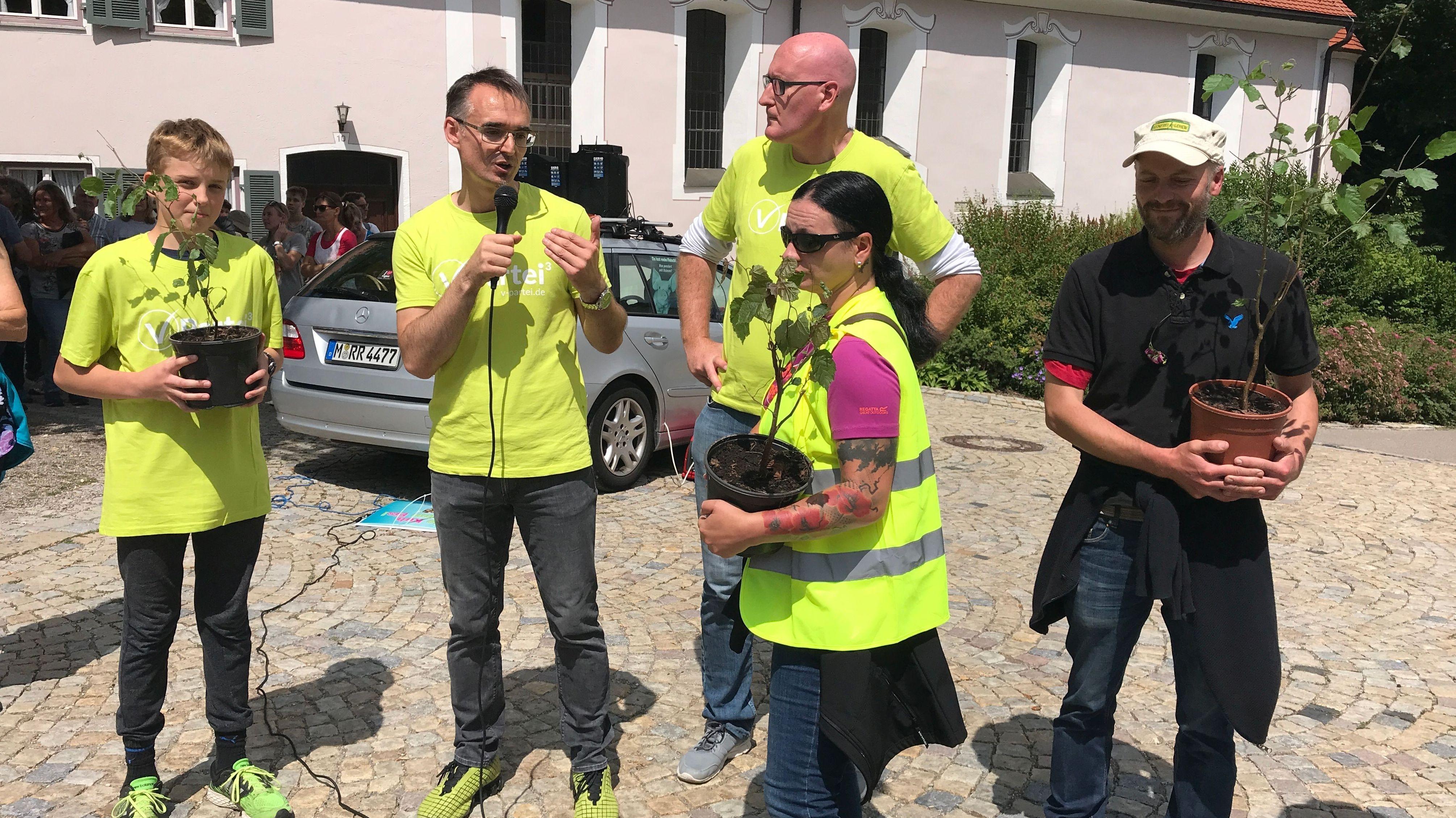 Gemeindevertreter erhalten Haselnuss-Sträucher als Zeichen für Nachhaltigkeit