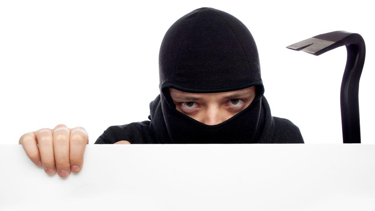 Ein maskierter Einbrecher mit einem Brecheisen (Symbolbild)