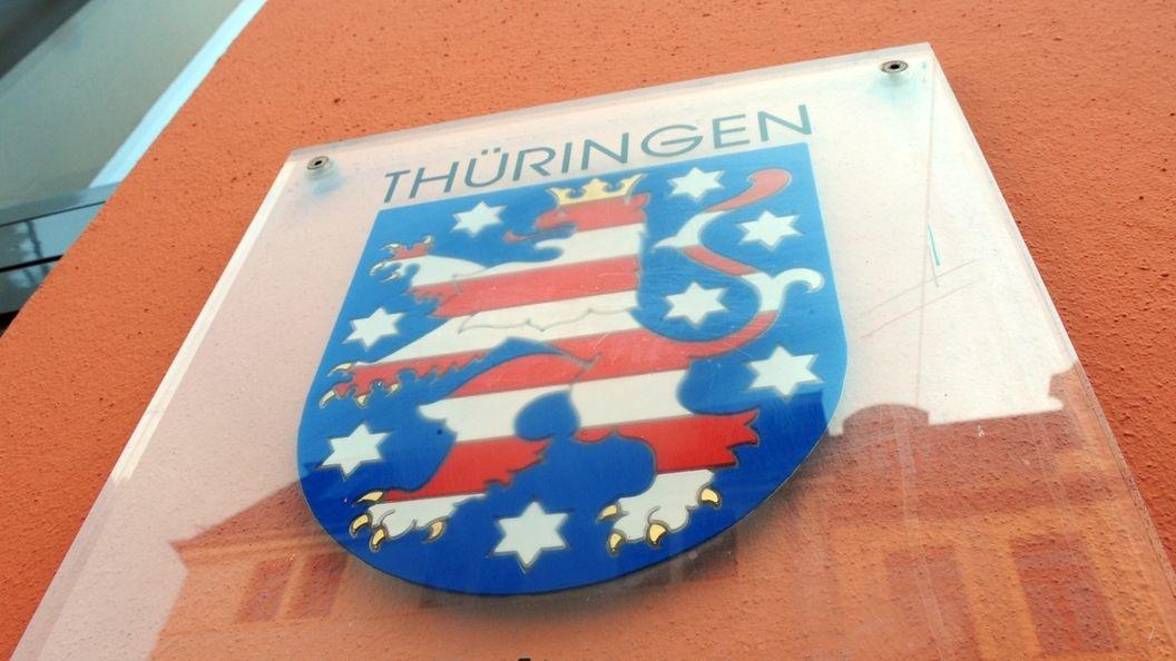 Das Wappen von Thüringen hängt an einer Hauswand