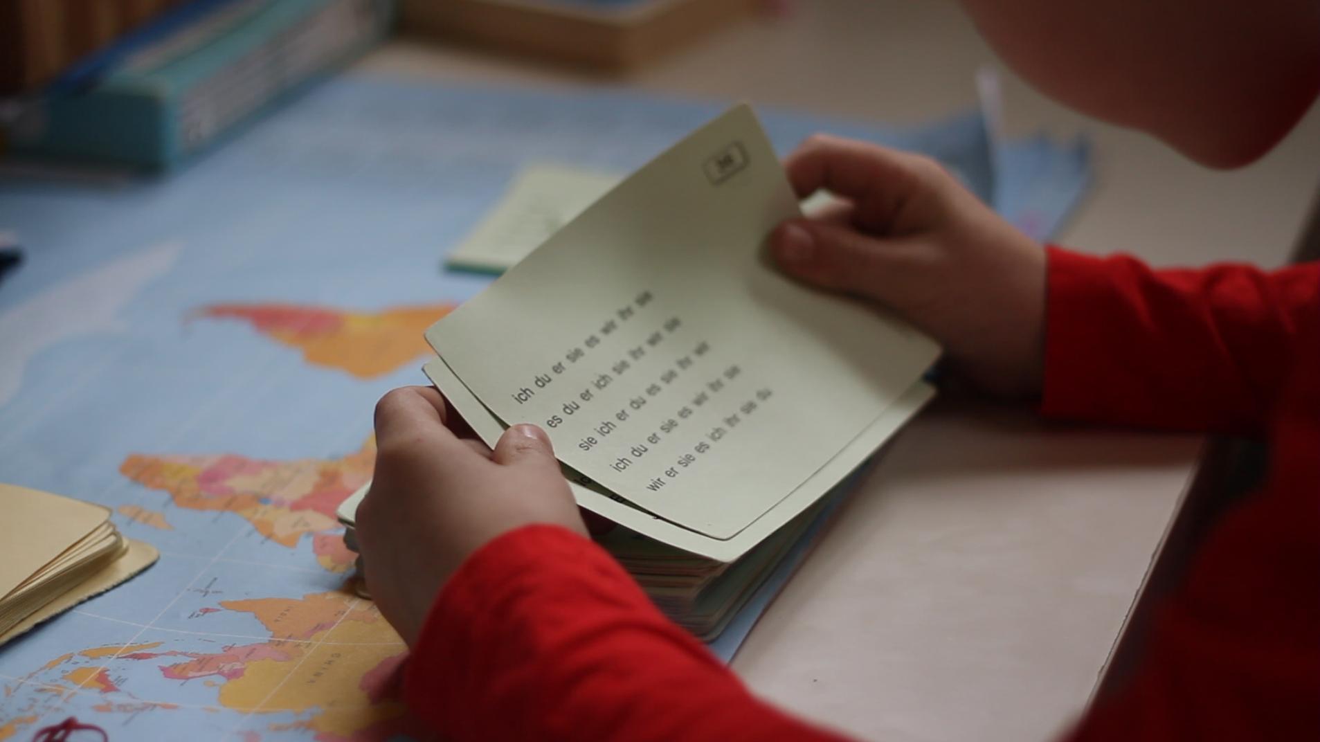 Robert bei der Lerntherapie. Er hält einen Zettel in der Hand, auf dem die Personalpronomen zu lesen sind.