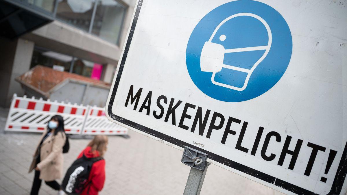 Ein Schild in einer Fußgängerzone macht auf die Maskenpflicht aufmerksam.