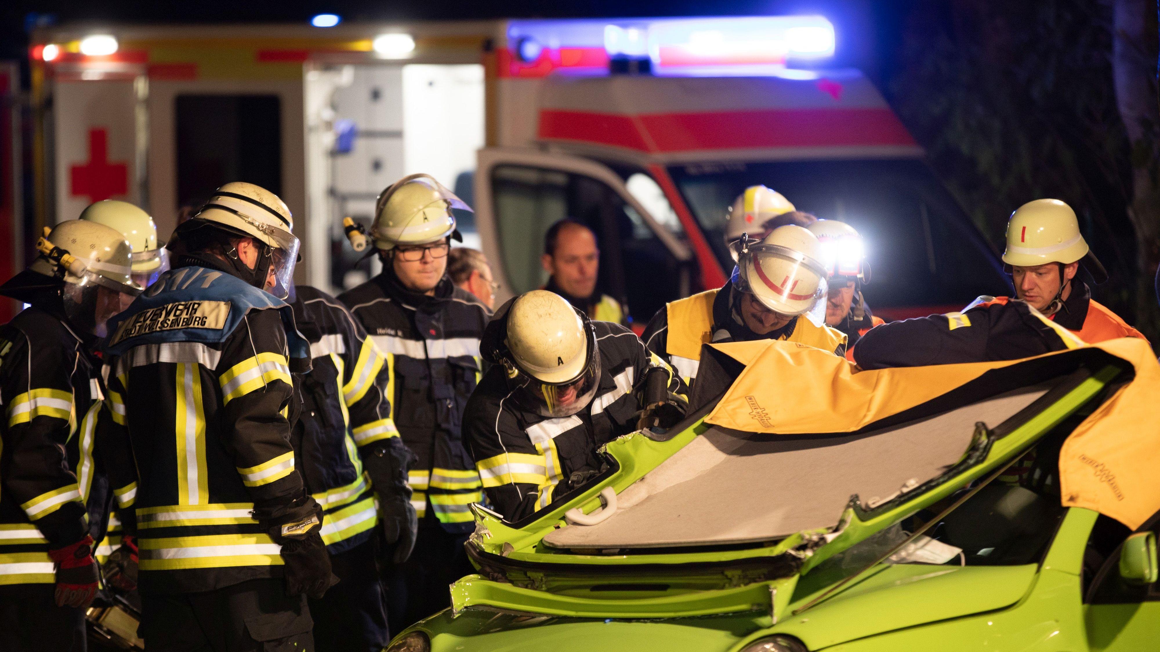 Mehrere Feuerwehrleute arbeiten an einem zerstörten Kleinwagen