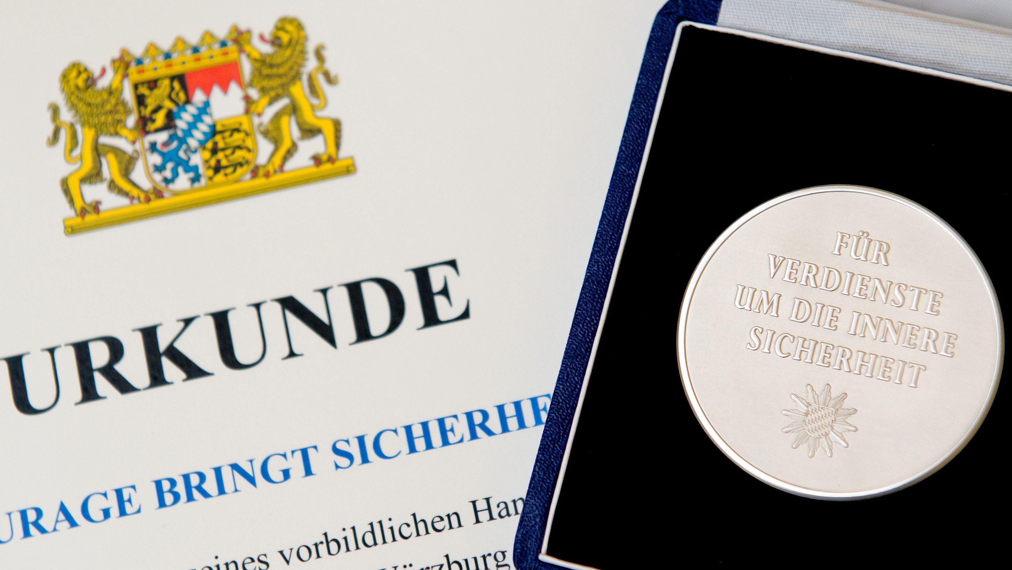 Eine Courage-Medaille und eine Urkunde liegen am 12.09.2014 in München vor der Verleihung durch den bayerischen Innenminister auf einem Tisch.