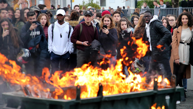 Schüler stehen im französischen Bayonne hinter einer brennenden Mülltonne.