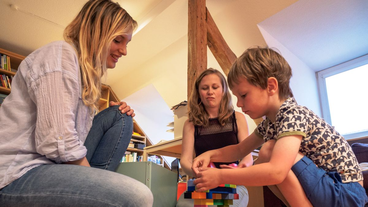 Katharina Frisch (M) sitzt zusammen mit ihrem vierjährigen Sohn Elijah (r) und dem italienischen Au-pair-Mädchen Francesca Righetti in ihrer Wohnung in Bamberg auf dem Boden.