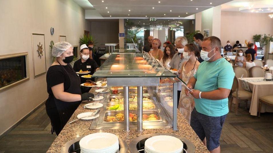 Touristen am Buffet, Mitarbeiter und Gäste mit Masken.