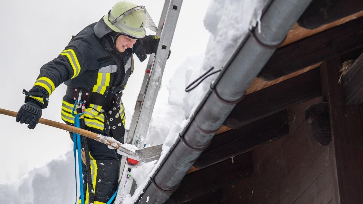 Bayern, Berchtesgaden: Ein Feuerwehrmann räumt ein mit Schnee überladenes Dach