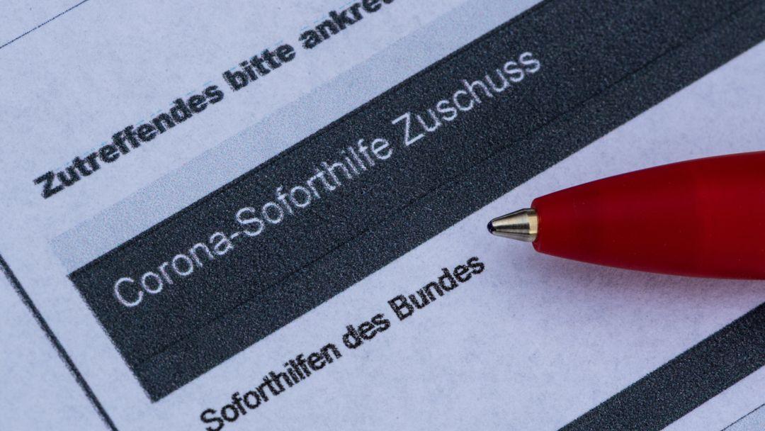 Kugelschreiber liegt auf Antragsformular für Corona-Soforthilfen
