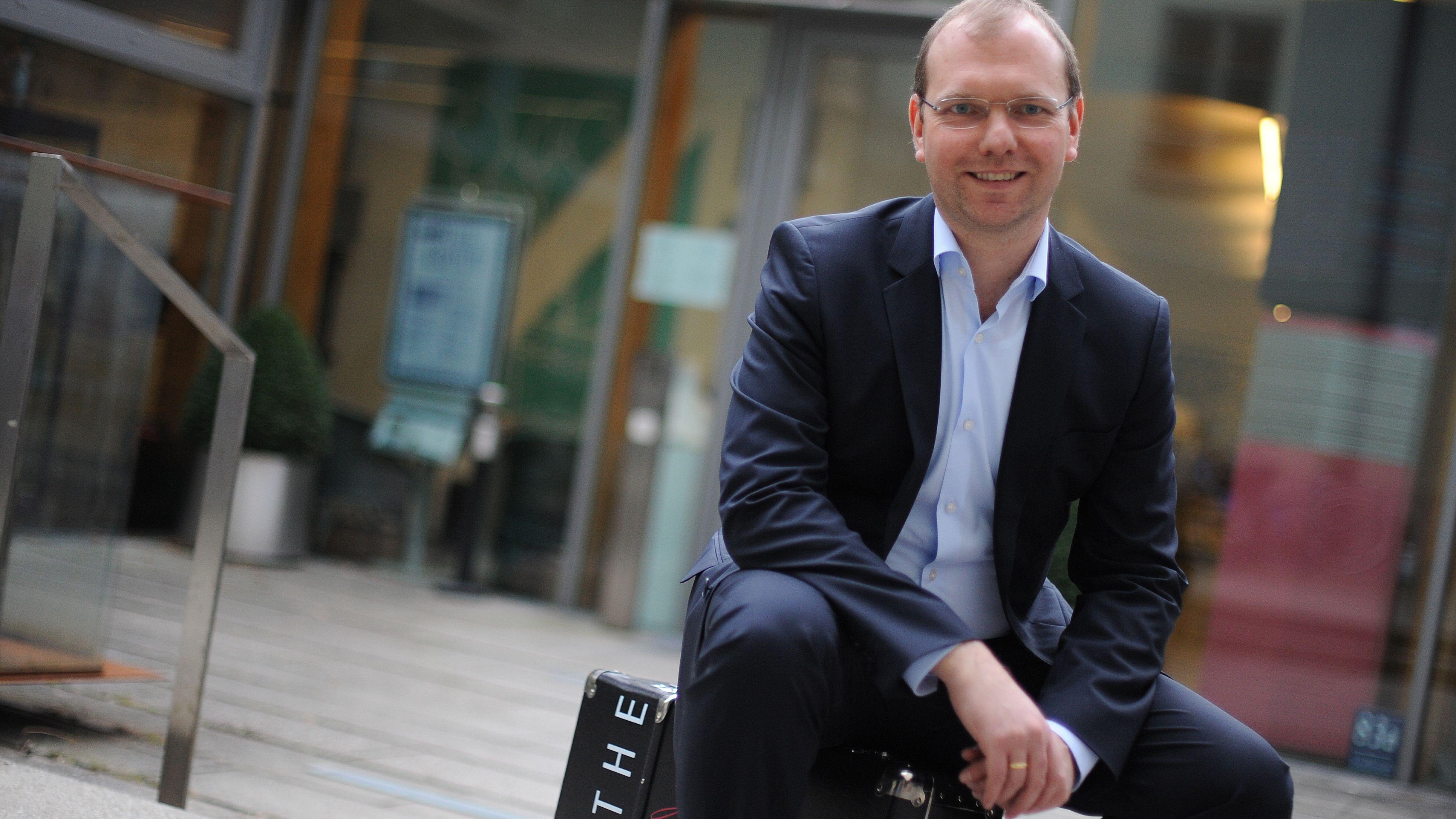 Holger Pils, Geschäftsführer der Stiftung Lyrik Kabinett sitzt in einem Innenhof auf einem Koffer