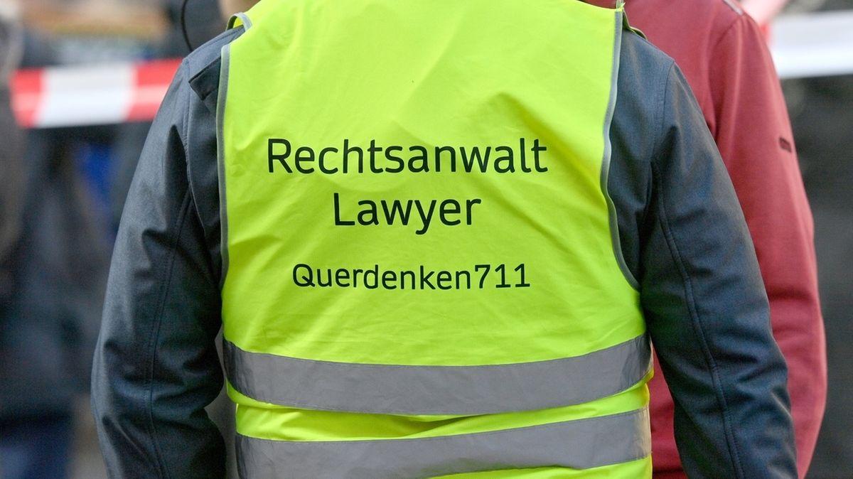 """Auf einer Kundgebung gegen die Maskenpflicht trägt ein Mann eine gelbe Weste mit der Aufschrift """"Lawyer"""", also Rechtsanwalt und dem Hinweis auf Querdenker"""