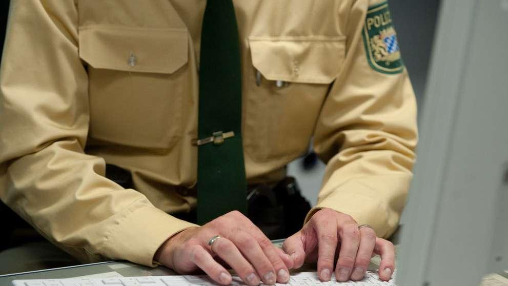 Polizist tippt Anzeige in seinen Computer - Symbolbild
