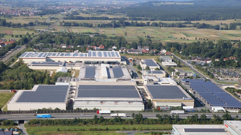 Produktionshallen und weitere Gebäude von Michelin in Hallstadt bei Bamberg aus der Vogelperspektive, im Hintergrund Wiesen und Bäume.