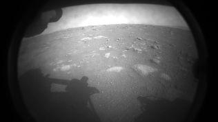Ein schwarzweißes Bild zeigt einen kleinen Ausschnitt der Marsoberfläche, im Vordergrund ist der Schatten des Rovers Perseverance zu sehen.