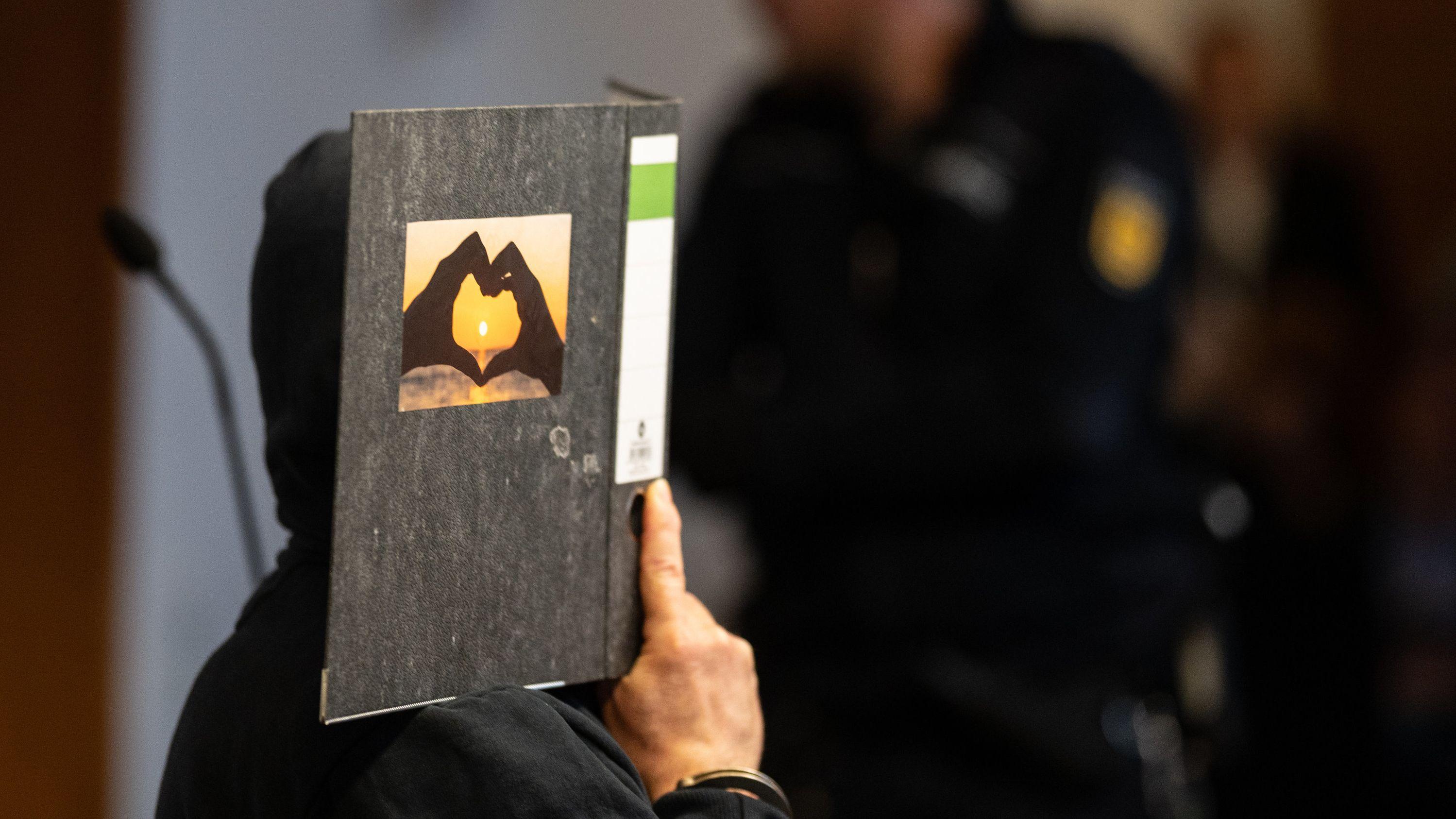 08.05.2019: Der 58-jährige Angeklagte im Fall  sitzt im Gerichtssaal im Landgericht und hält einen Aktenordner mit einem Herz aus zwei Händen vor sein Gesicht