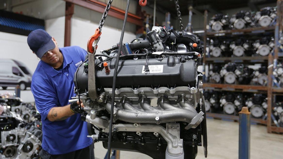 Ein Mann arbeitet an einem Motorblock für ein Fahrzeug. (Symbolbild)