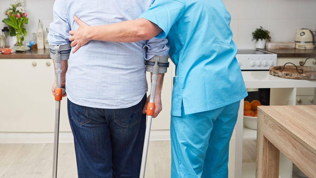 Therapeutin macht Physiotherapie und hilft einem Mann auf Krücken