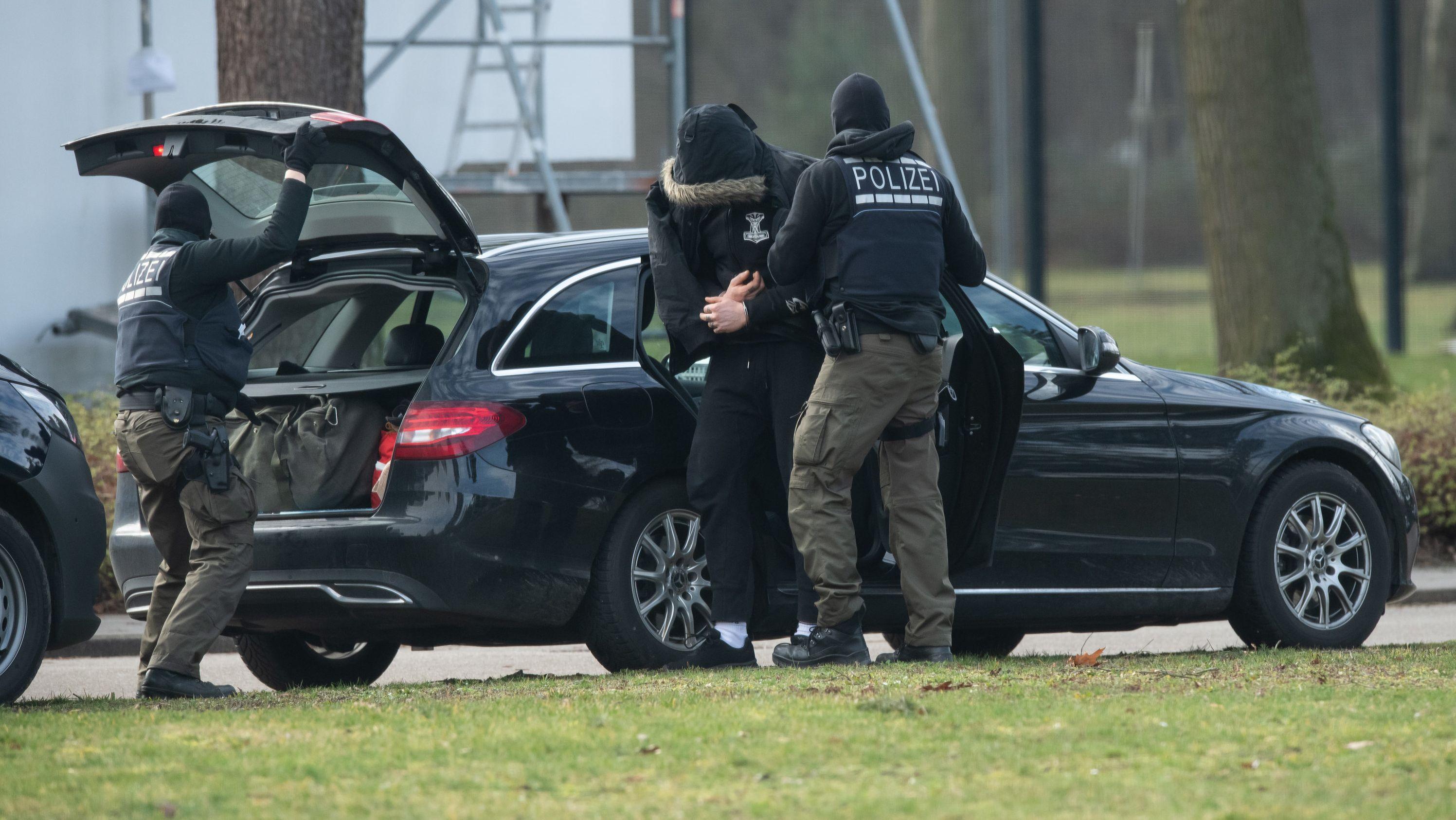 Eine Person wird von Polizisten in den Bundesgerichtshof gebracht. Einen Tag nach der Zerschlagung einer mutmaßlichen rechten Terrorzelle sind die ersten Festgenommenen in Karlsruhe zu Haftrichtern des Bundesgerichtshofs (BGH) gebracht worden.