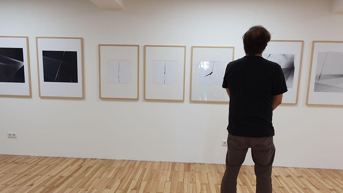 Ein Mann betrachtet mehrere an der Wand hängende Zeichnungen.