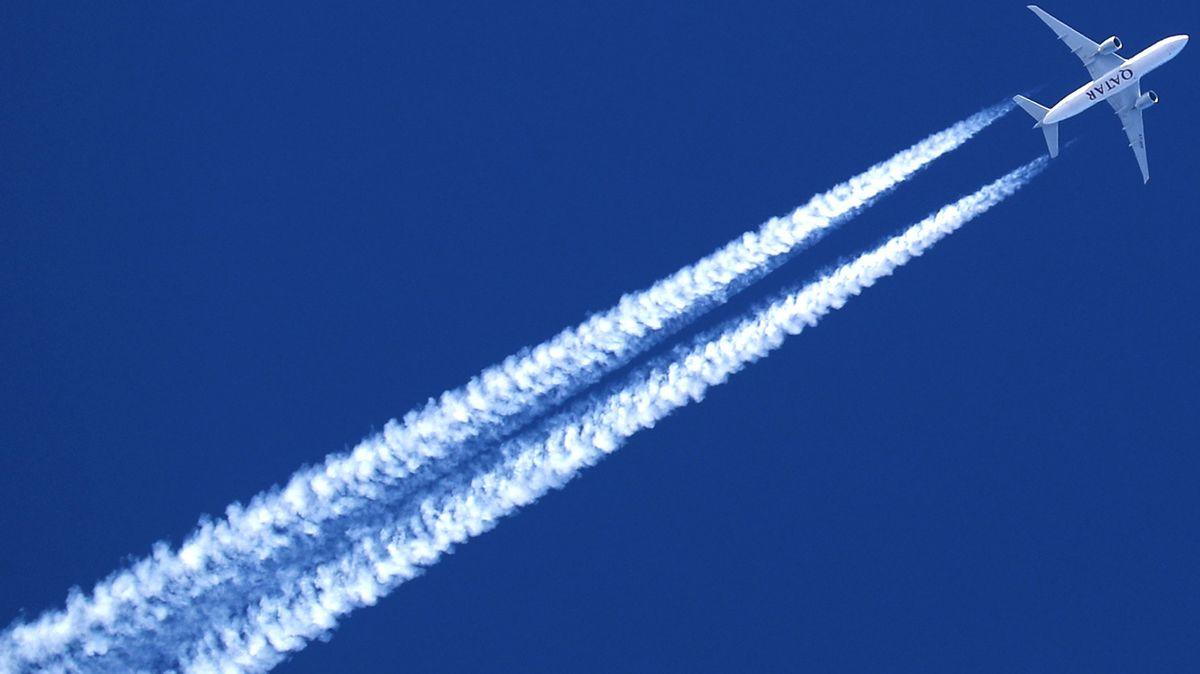 Ein Flugzeug am Himmel, dahinter ein langer Kondensstreifen