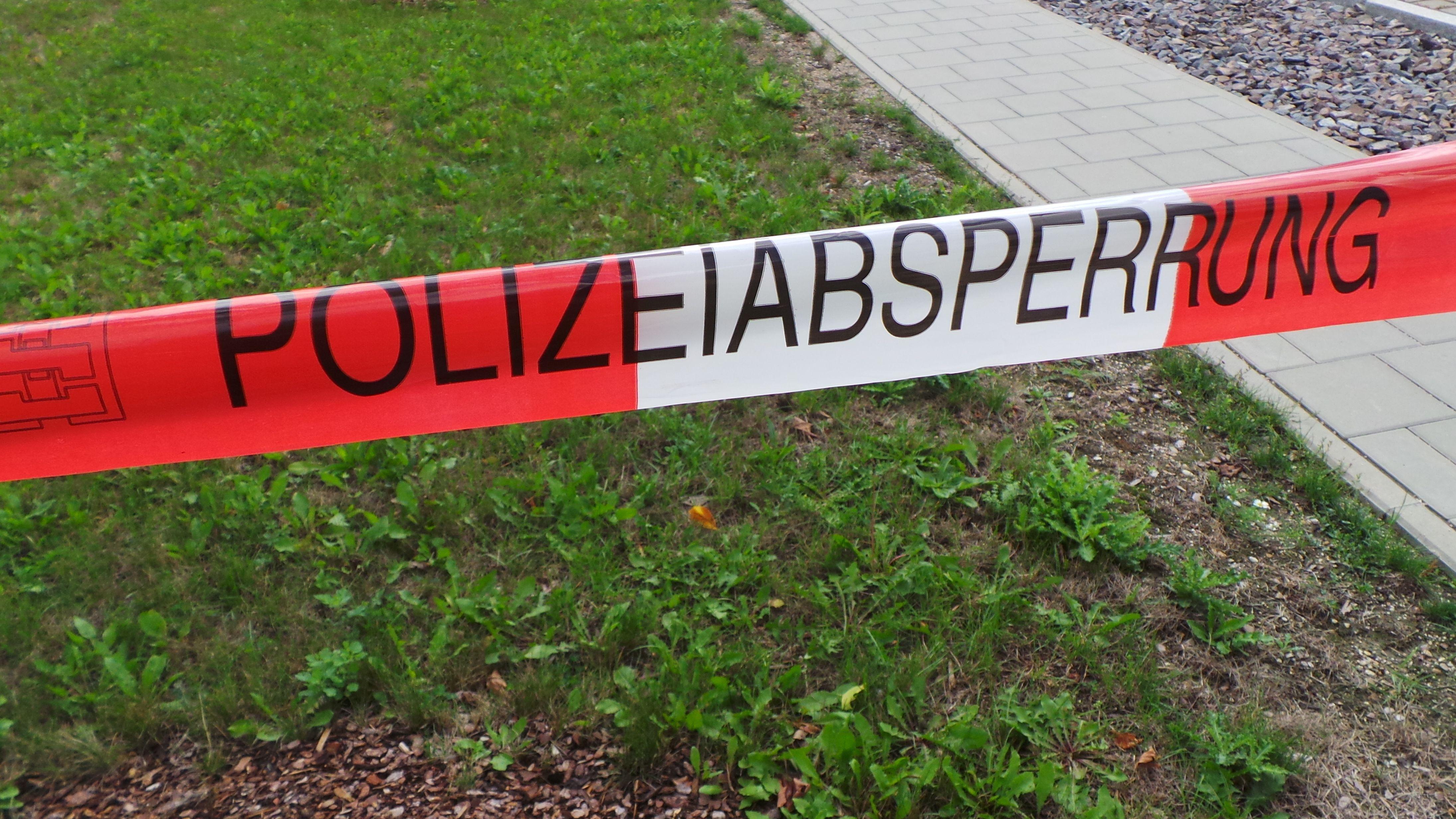 """rot-weiß Absperrrband, darauf der Text: """"Polizeiabsperrung"""""""