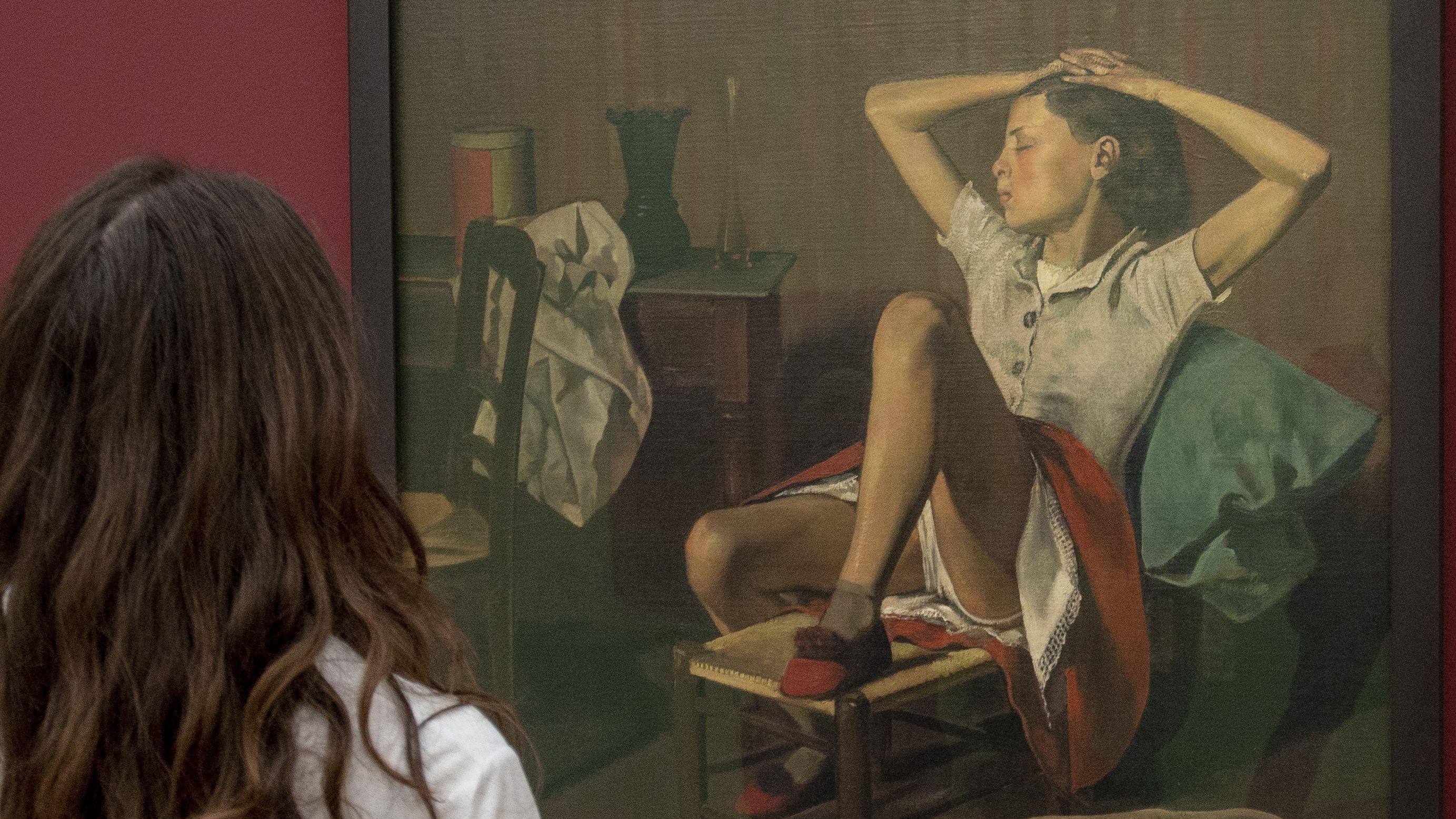 """Eine Frau mit langen braunen Haaren schaut sich Balthus' Gemälde  """"Thérèse träumend"""""""