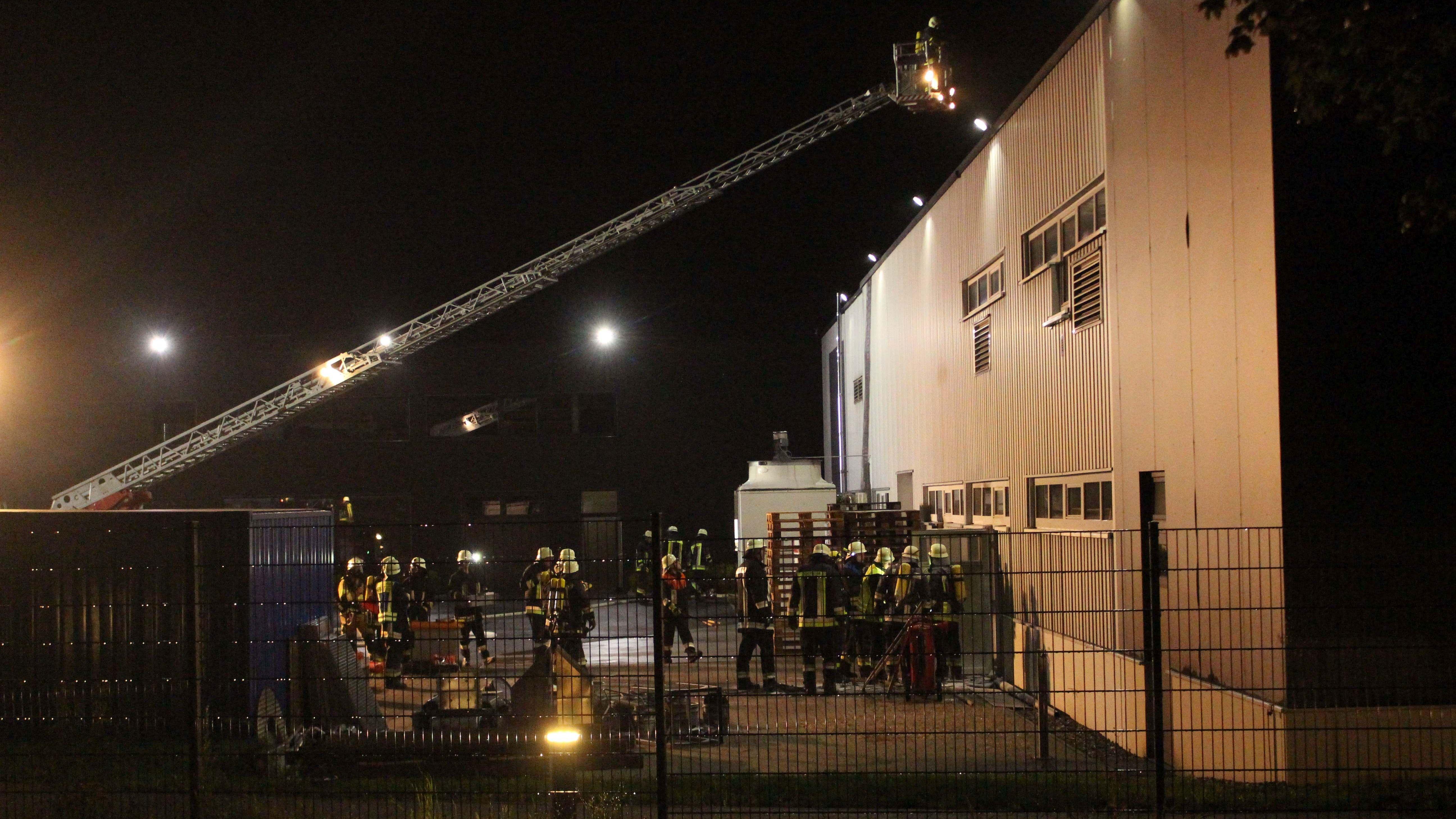 Feuerwehrleute mit Leiter vor und auf der Fabrikhalle.