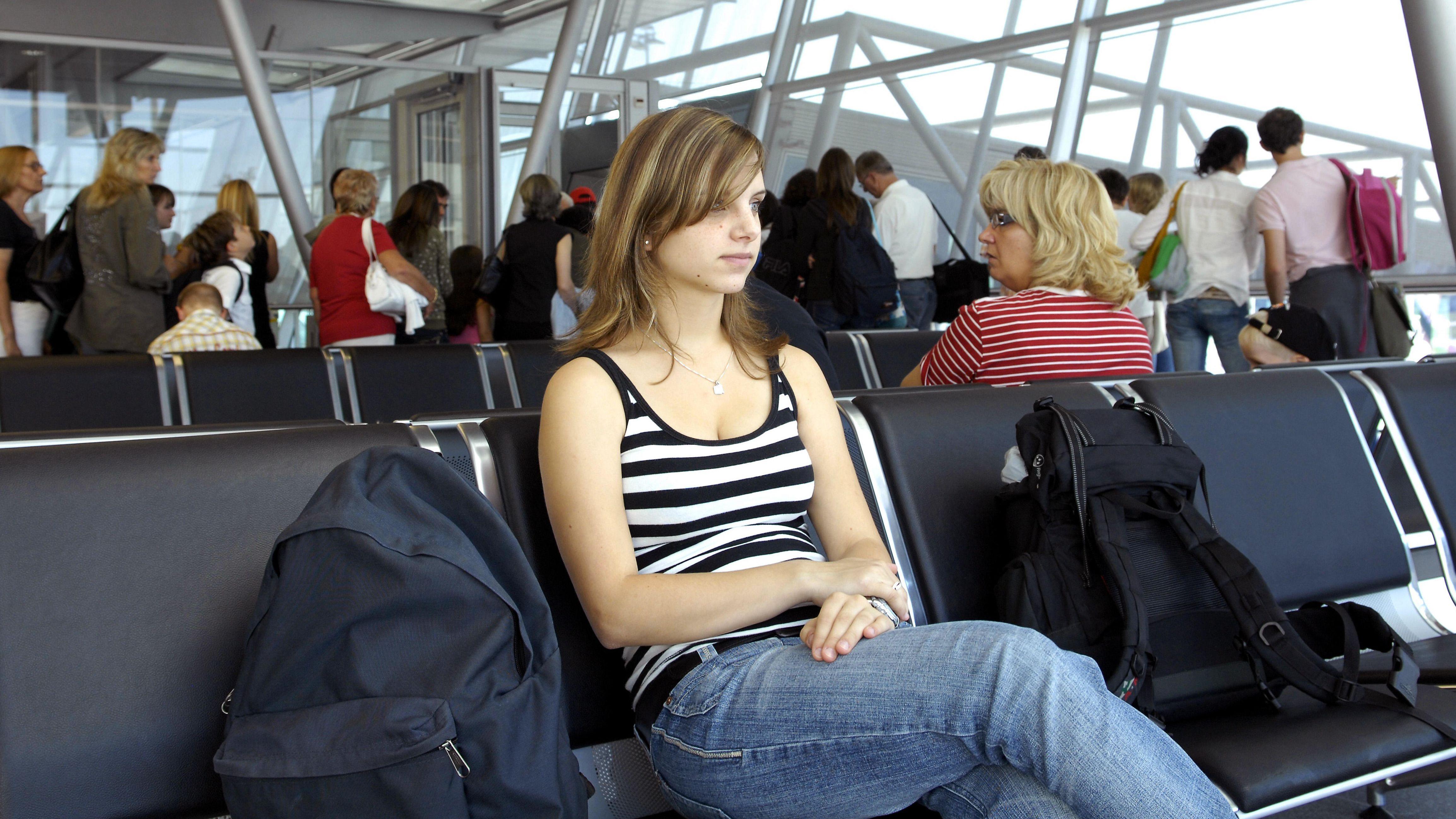 Junge Frau sitzt und wartet am Flughafen.