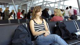 Junge Frau sitzt und wartet am Flughafen. | Bild:picture alliance / blickwinkel