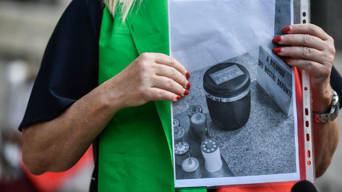 Eine Angehörige zeigt das Foto eine Urne