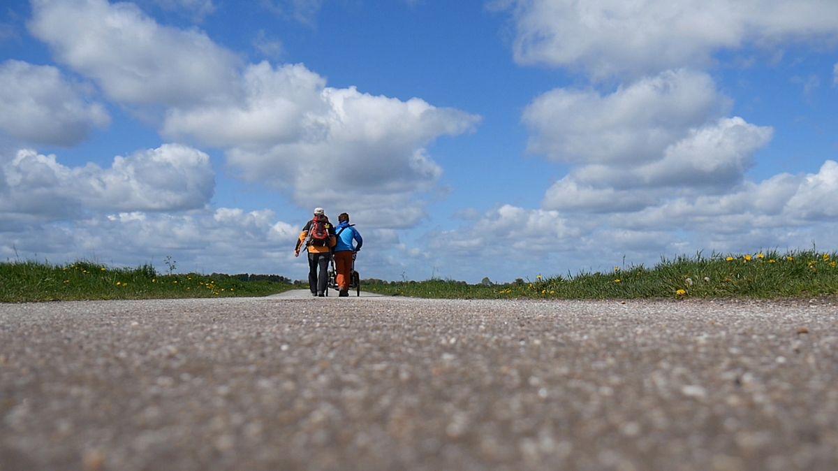 Susanne und Walter Wärthl sind von hinten auf einer Straße zu sehen, wie sie den Kinderwagen mit Gepäck schieben.
