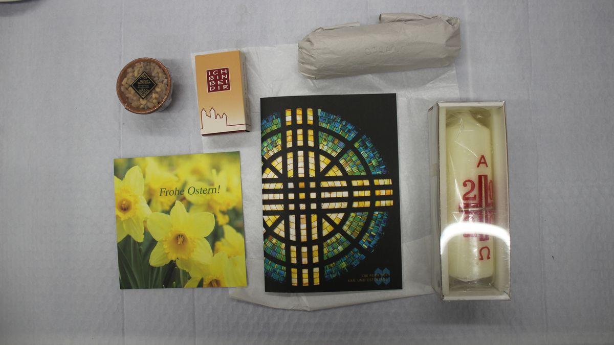 Weihrauch in einem Schälchen, Hefte, in Papier eingewickelte Kohle und eine Kerze liegen auf einem Tisch.